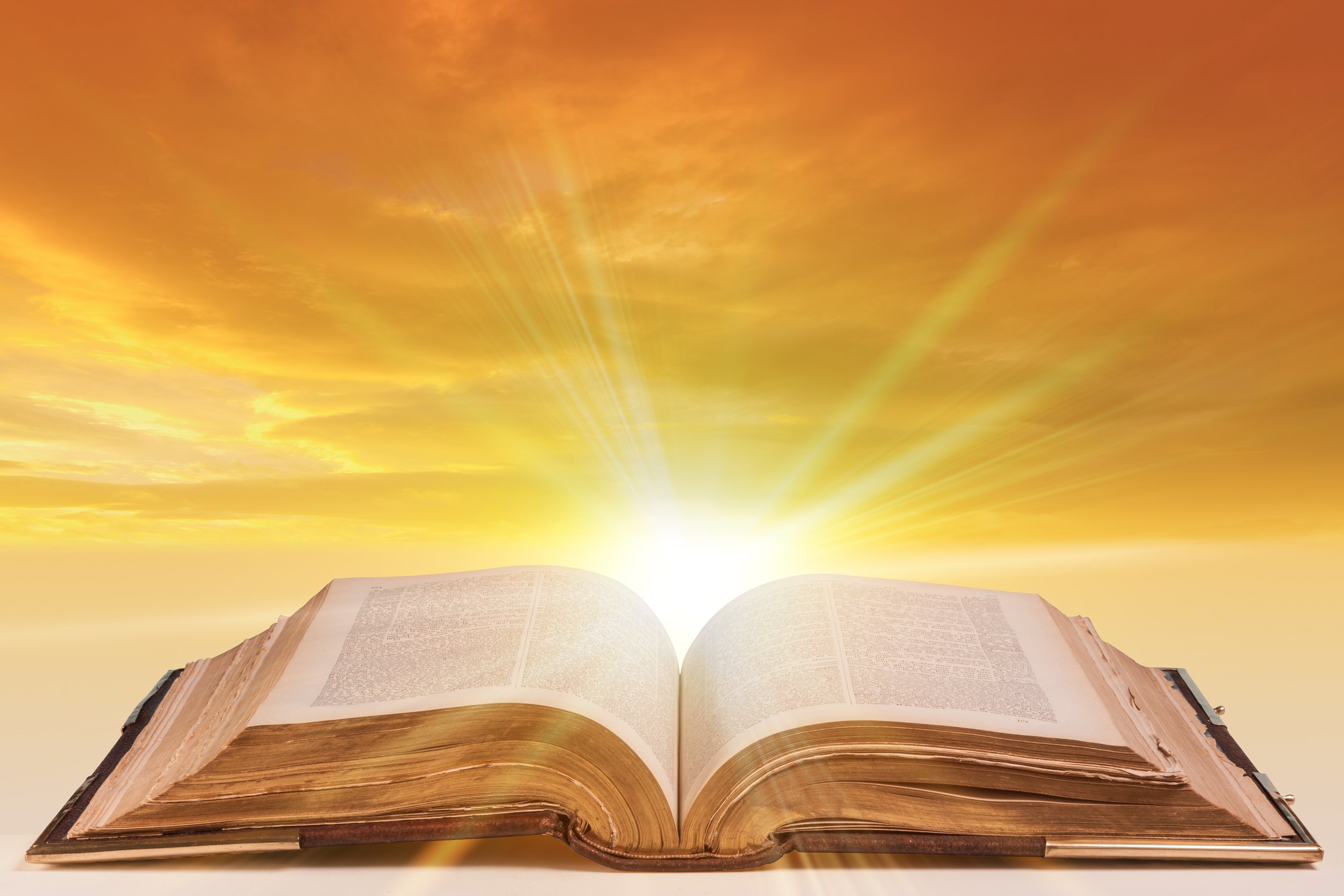 old antique bible as an open book with sunlight bursting from the pages