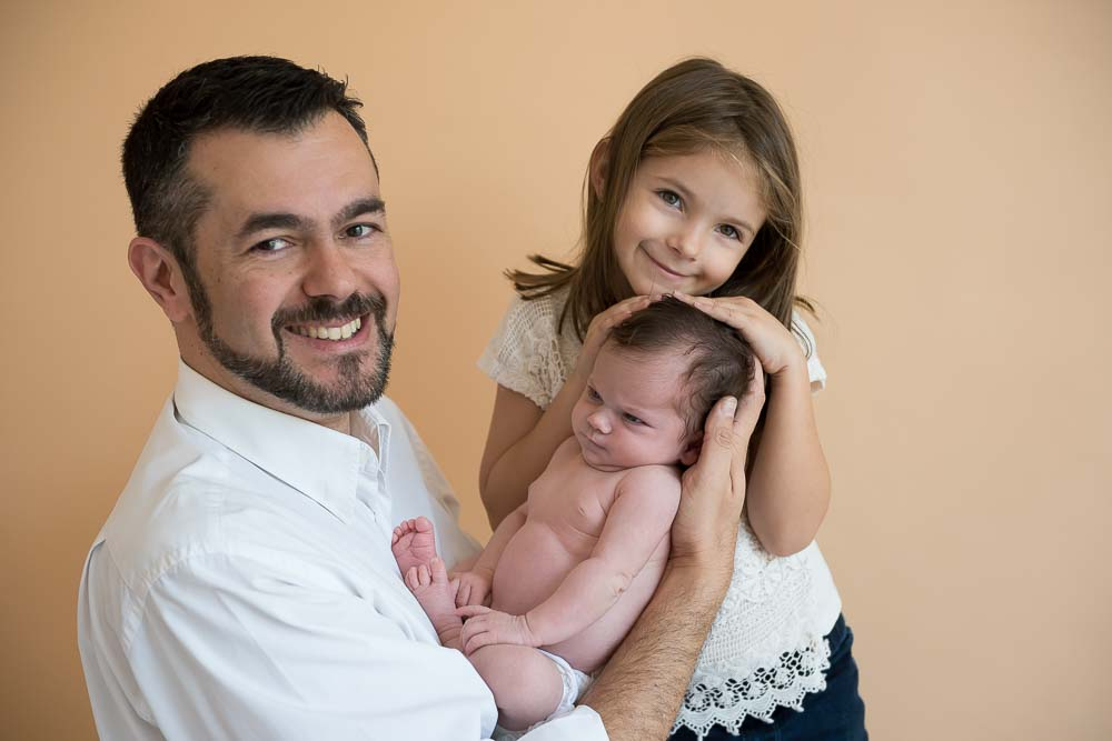 pai com recém-nascida e filha mais velha em ensaio newborn no estúdio fotográfico laura alzuera