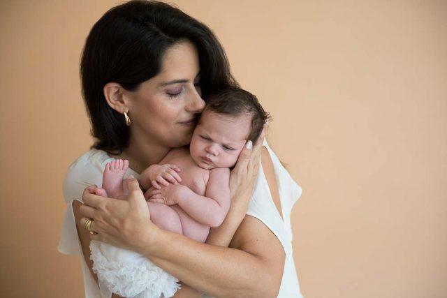 mãe beijando filha recém-nascida em ensaio newborn no estúdio fotográfico laura alzueta em São Paulo