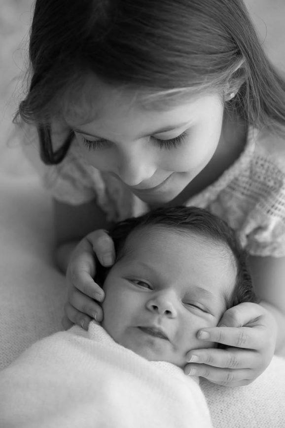 foto preta e branca mãe beijando filha recém-nascida em ensaio newborn no estúdio fotográfico laura alzueta em São Paulo