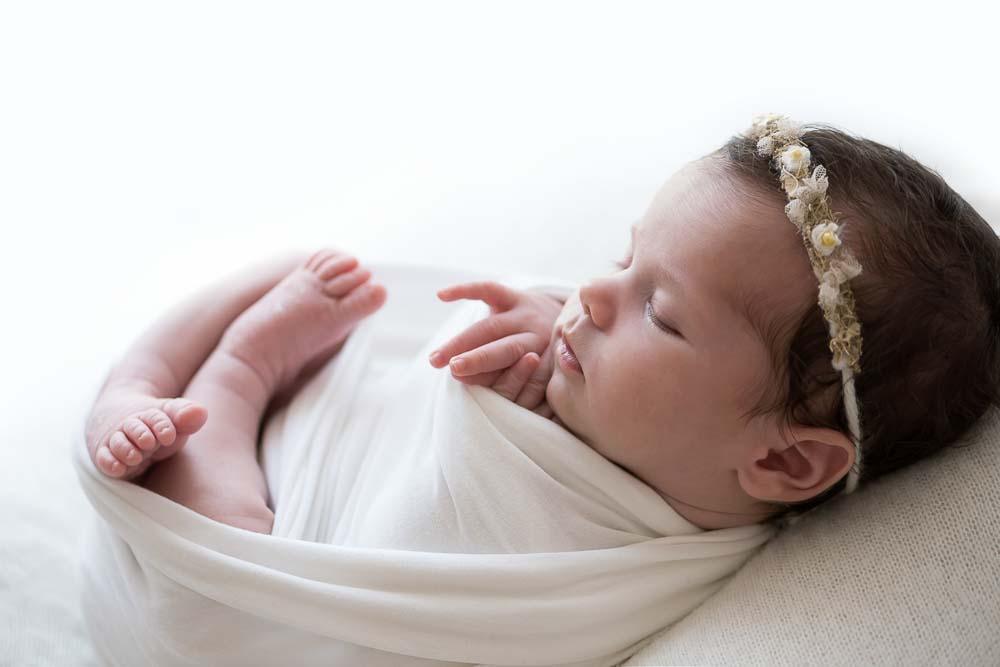 recém-nascida em em posição enrolada com wrap ensaio newborn no estúdio fotográfico laura alzueta em São Paulo