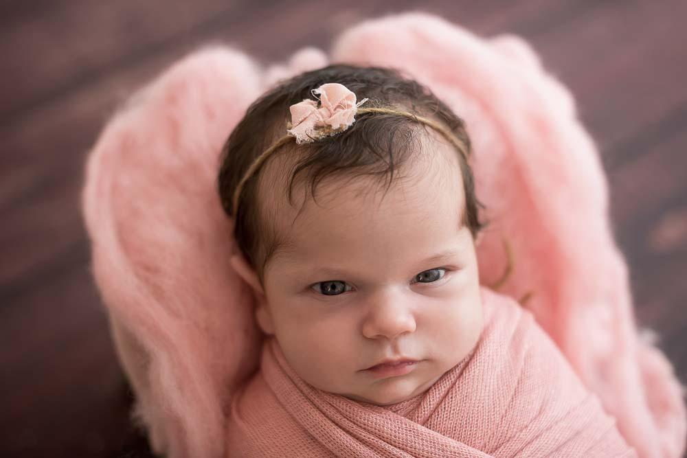 recém-nascida com arco na cabeça em ensaio newborn no estúdio fotográfico laura alzueta em São Paulo