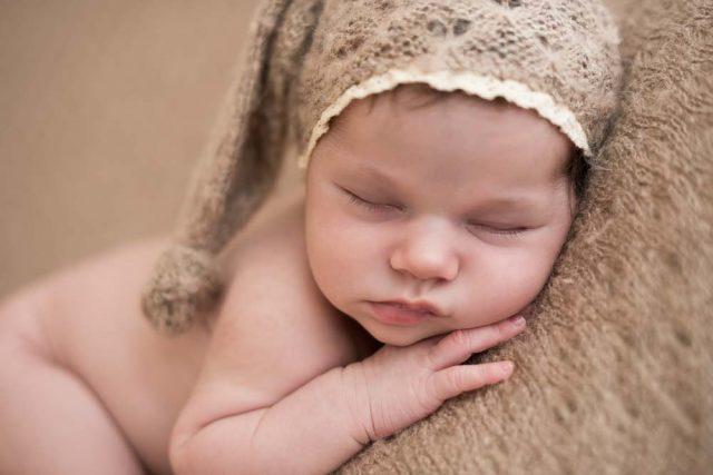 recém-nascida com gorro bege na cabeça em ensaio newborn no estúdio fotográfico laura alzueta em São Paulo