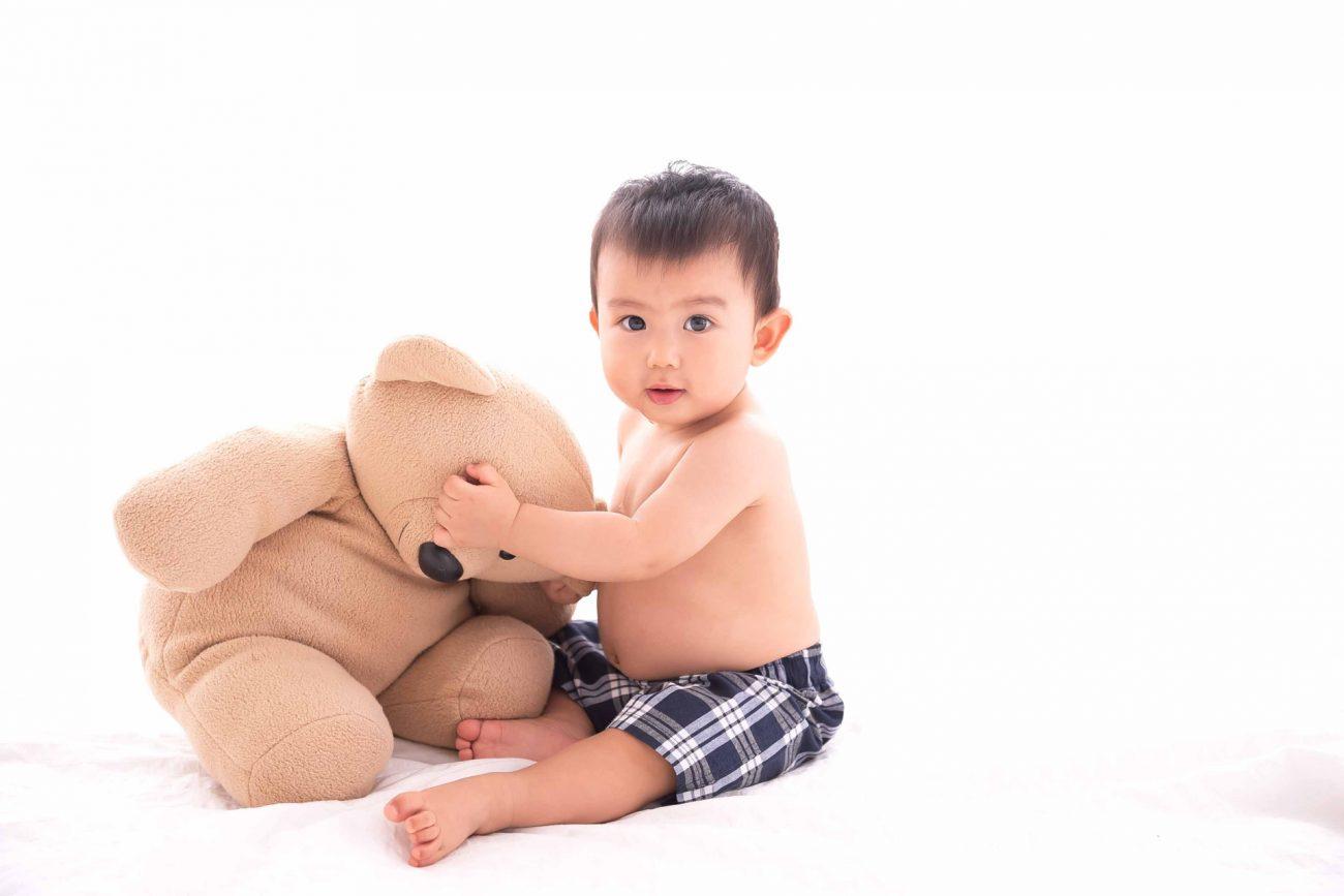 bebê segurando ursinho em sessão de fotos de acompanhamento de bebês em estúdio fotográfico são paulo