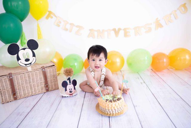 aniversário de 1 ano smash the cake família pai mãe e bebê em sessão de fotos de acompanhamento de bebês em estúdio fotográfico são paulo