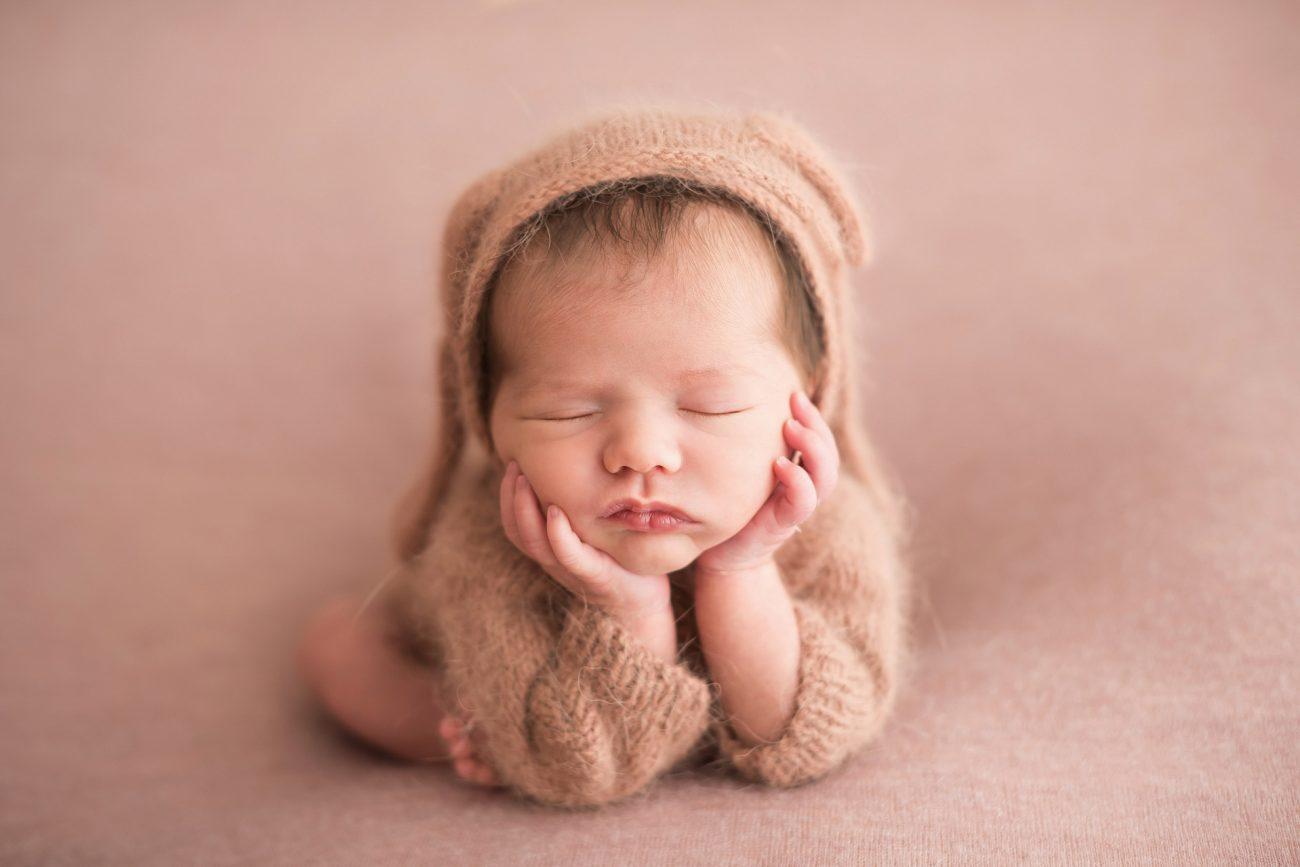 bebê fofo com as mãos no queixo com touca bege estúdio de fotografia newborn como fazer o atendimento aos clientes