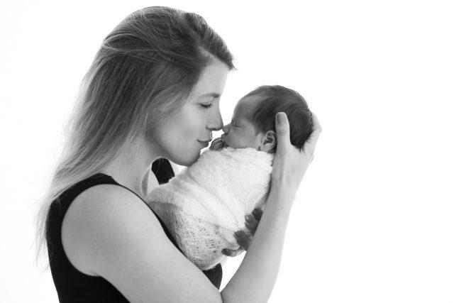 foto preta e branca de mãe beijando filha recém-nascida enrolada em wrap em estúdio de fotografia newborn