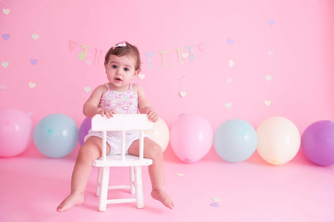 bebê sentada em cadeira com fundo rosa com balões candy colors smash the cake laura alzueta estúdio de fotografia são paulo ensaio de fotos de aniversário de 1 ano de bebê menina