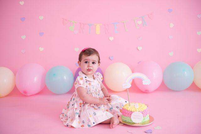 bolo colorido com arco-íris bebê sentada em cadeira com fundo rosa com balões candy colors smash the cake laura alzueta estúdio de fotografia são paulo ensaio de fotos de aniversário de 1 ano de bebê menina