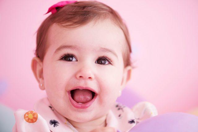 bebê menina com laço na cabeça sorrindo smash the cake laura alzueta estúdio de fotografia são paulo ensaio de fotos de aniversário de 1 ano de bebê menina
