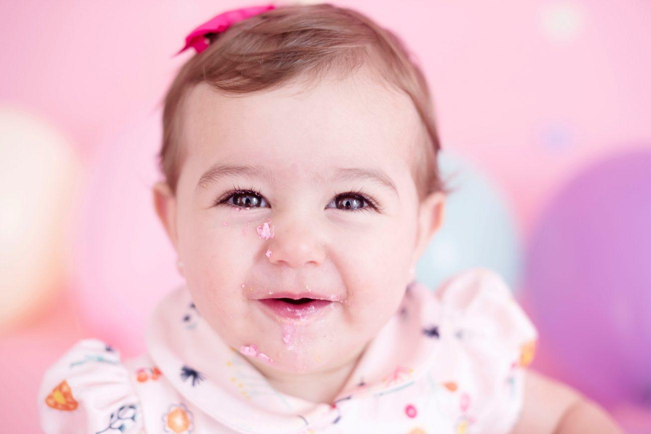 bebê fofo com laço rosa na cabeça smash the cake laura alzueta estúdio de fotografia são paulo ensaio de fotos de aniversário de 1 ano de bebê menina