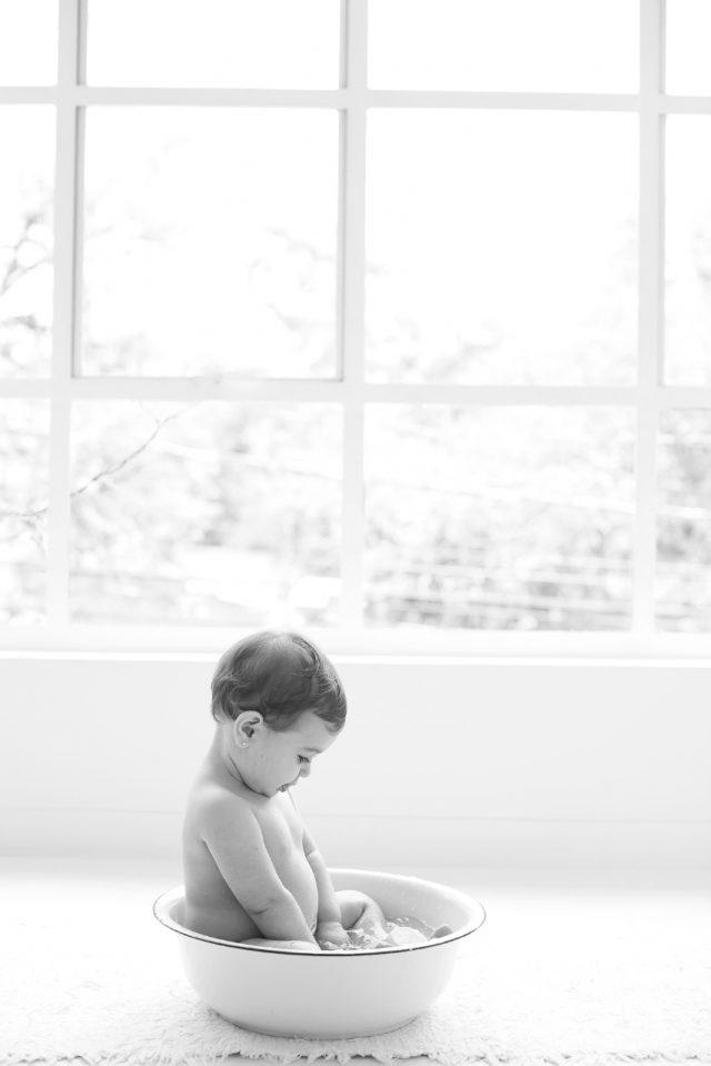 bebê tomando banho em banheira com janela ao fundo smash the cake laura alzueta estúdio de fotografia são paulo ensaio de fotos de aniversário de 1 ano de bebê menina