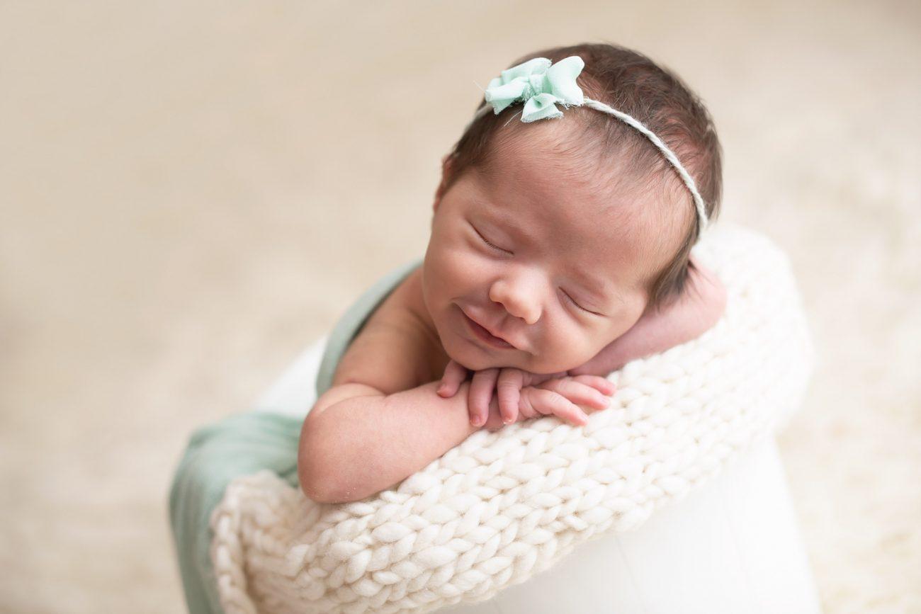 ensaio de fotos com bebê recém-nascido com tiara no cabelo e de olhos fechados em estúdio de fotografia newborn laura alzueta na zona oeste de são paulo