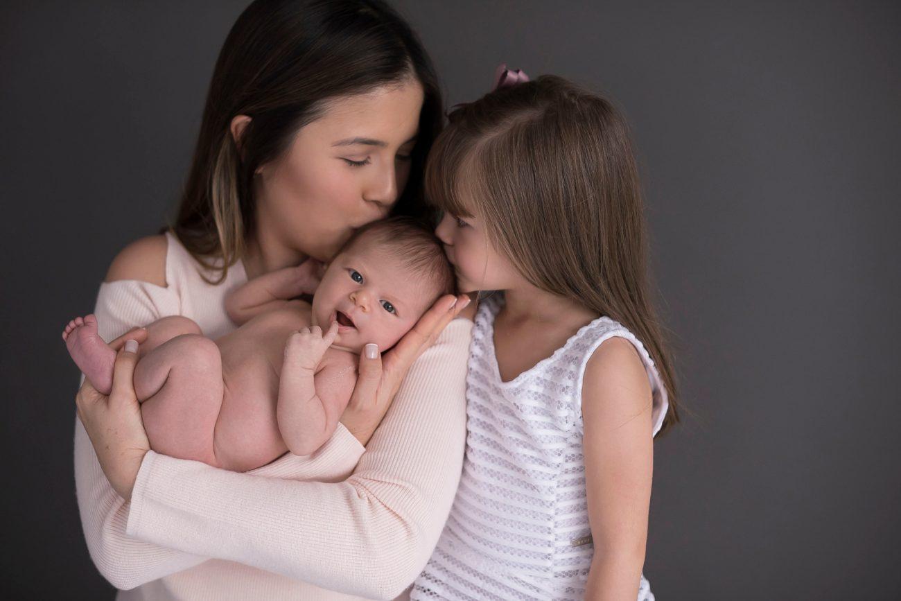 ensaio newborn com irmãos mãe e filha dando beijo no bebê foto por laura alzueta