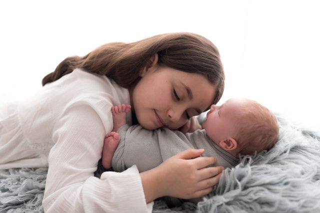 ensaio newborn com irmãos menina abraça com carinho irmão recém nascido foto por laura alzueta
