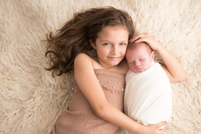 ensaio newborn com irmãos menina mais velha com bebê recem nascido em fotos do estúdio fotografico laura alzueta