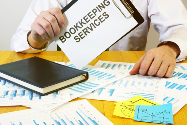 """A person sitting at a desk with papers and books. They're holding a clipboard that says """"bookkeeping services."""""""