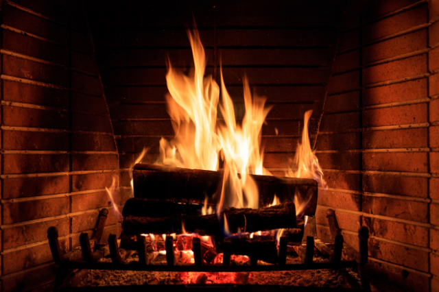 Close up of a fire burning in a brick fireplace
