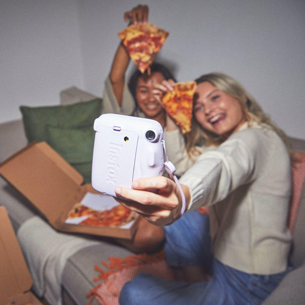duas meninas comendo pizza e tirando fotos com câmera Instax Mini 11