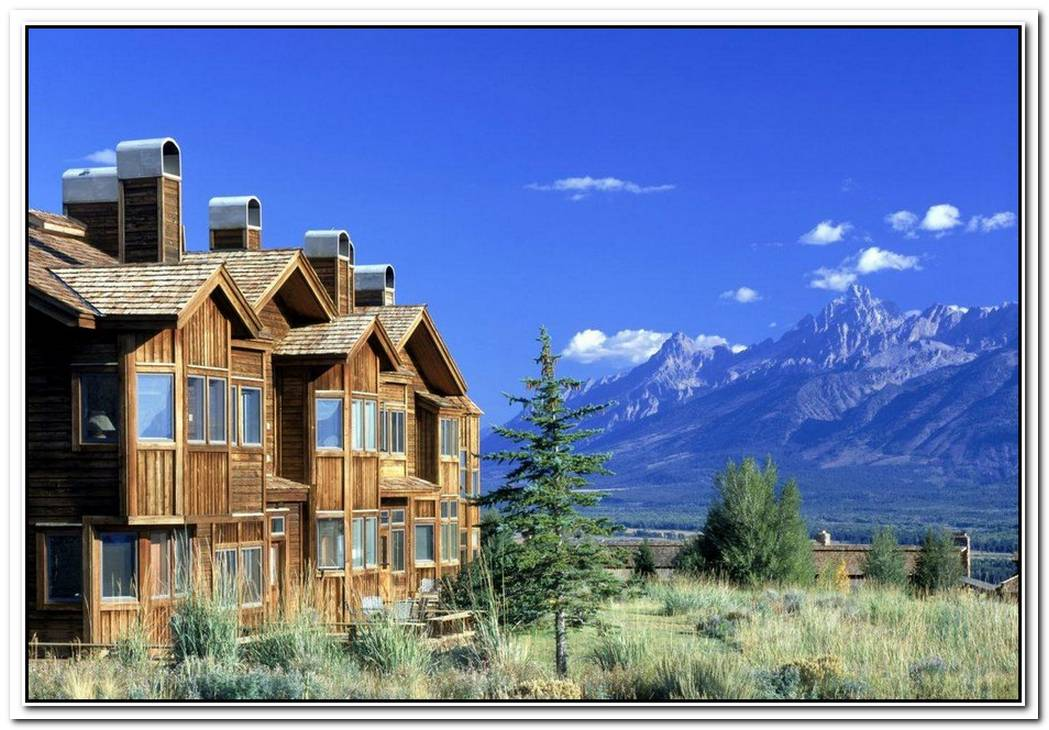 A House In Wyoming Caught Between Mountains And A Steam