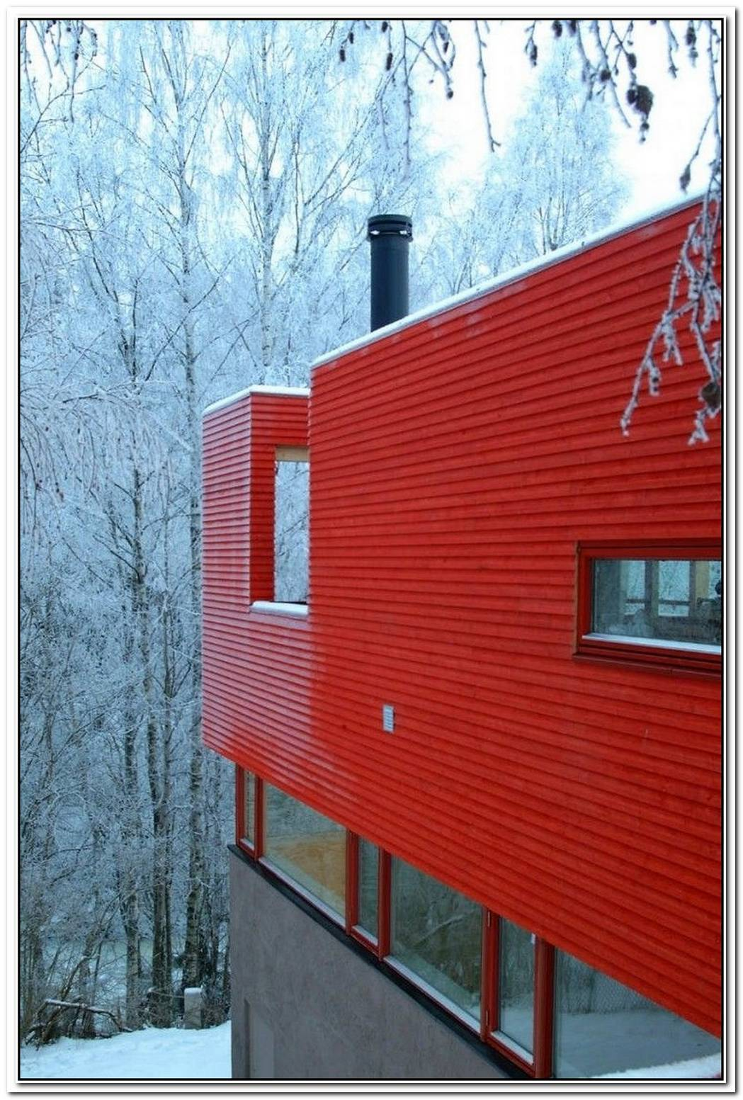 Bright Red House Nestled In A Norwegian River Valley