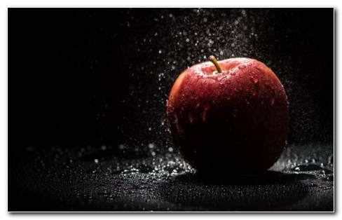 A Red Apple In Black Background With Splashing Water On It