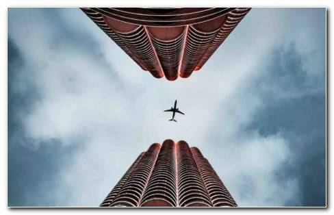 Bottom View Of Two Red Skyscraper Buildings And A Plane Flying Above Them