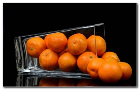 Tangerines VS Oranges. Tangerines And Oranges In A Glass.