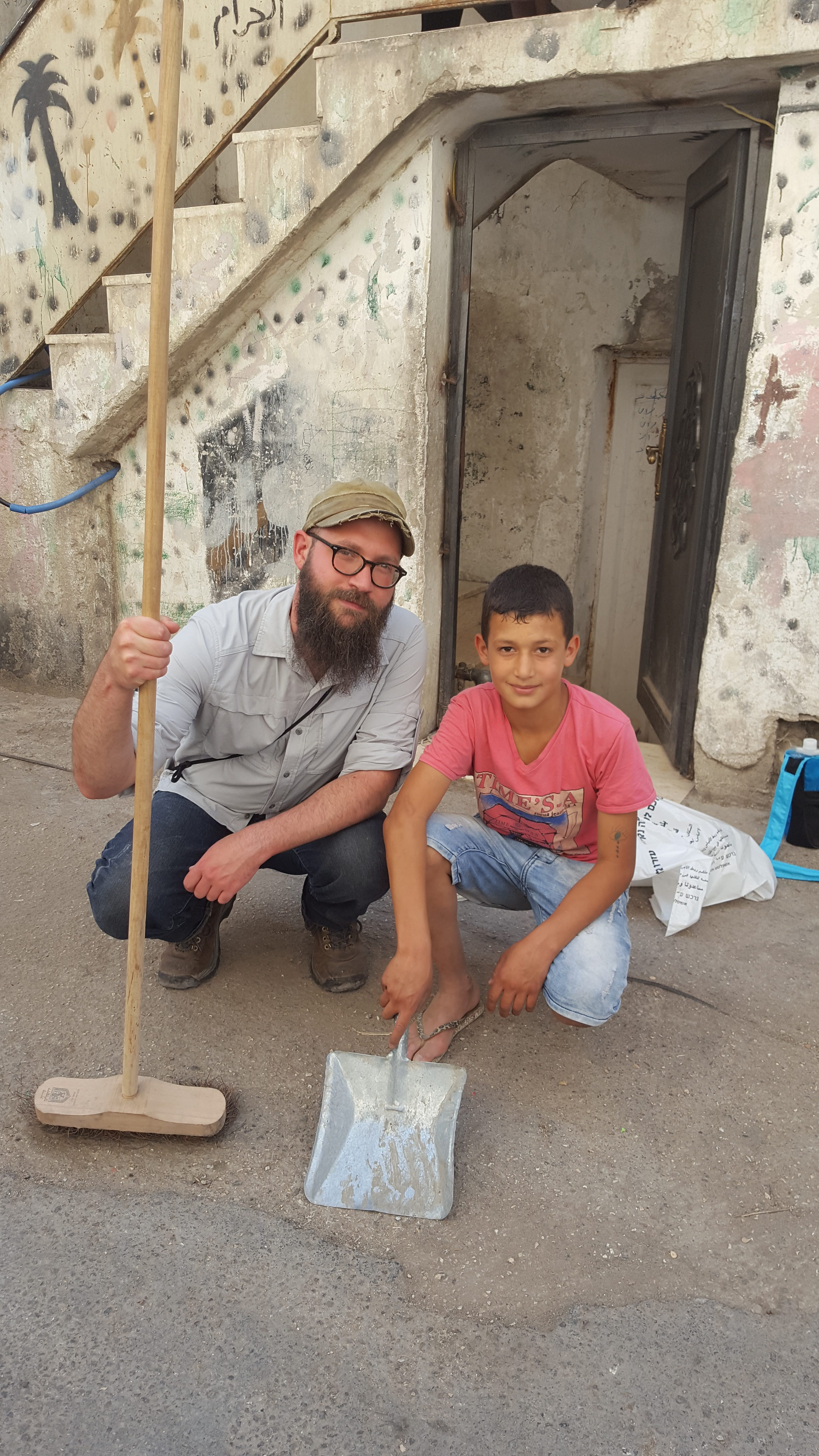 Justin cleaning the streets of Batan al-Hawa in East Jerusalem with one of our hosts, copyright Alana Alpert