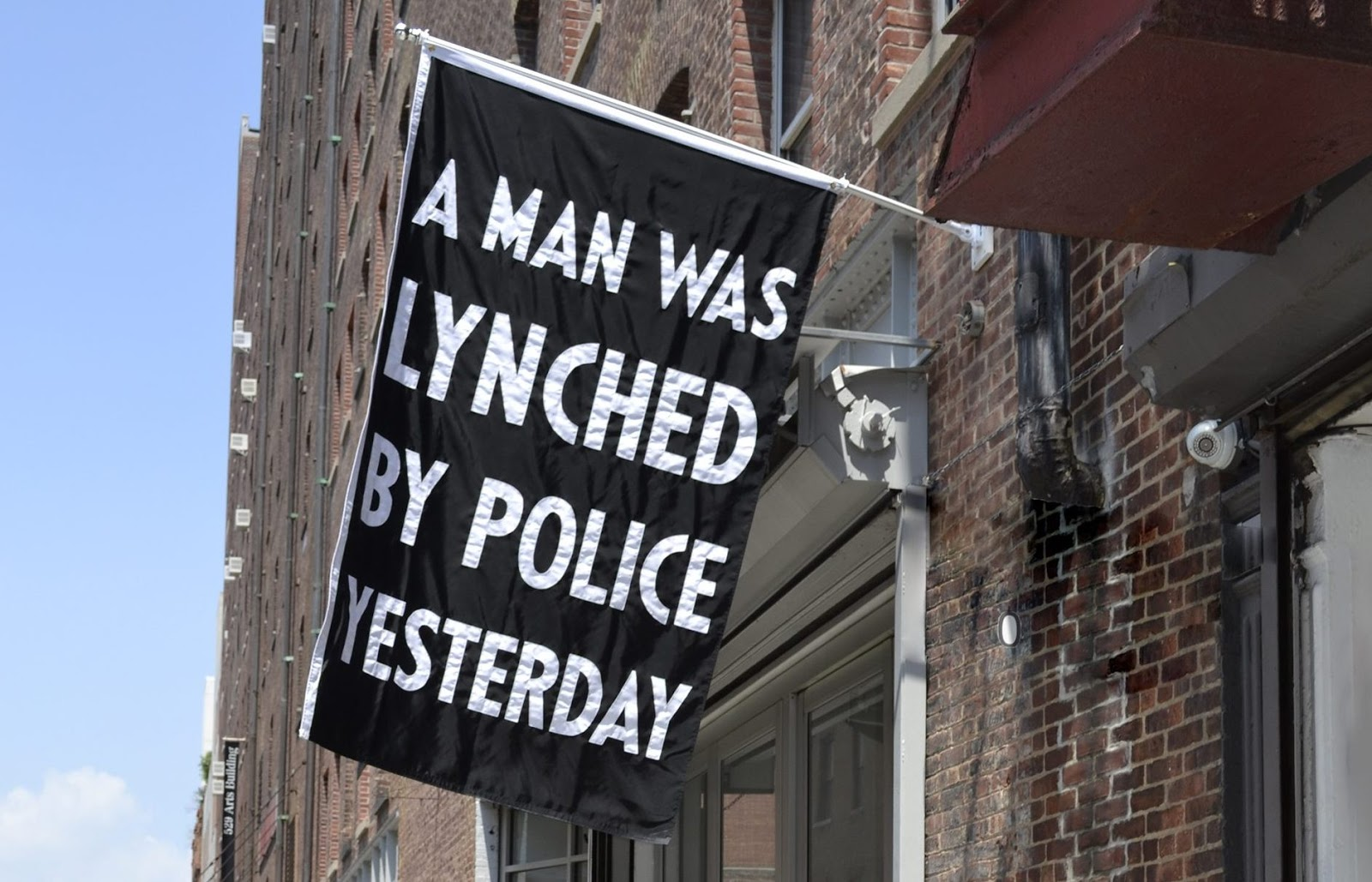 "A banner reading ""A man was lynched by police yesterday"" by artist Dread Scott protests contemporary police violence by referencing the flag hung by the NAACP to condemn lynchings of the 1930s."