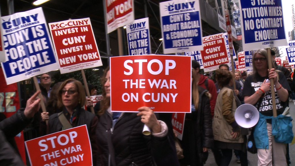 "Protest signs ""Stop the War on CUNY"" and ""Invest in CUNY, Invest in NY"" at protests against budget cuts to City University of New York"